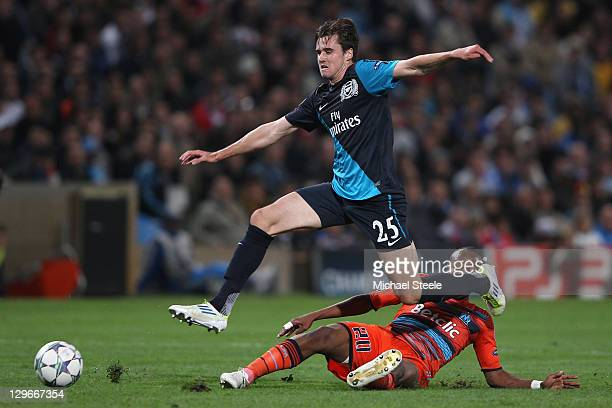 Carl Jenkinson of Arsenal hurdles a challenge from Andre Ayew during the UEFA Champions League Group F match between Olympique de Marseille and...