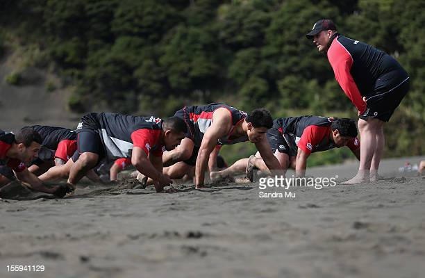 Carl Jennings Warriors strength and conditioning coach watches players train on the sand dunes during the New Zealand Warriors NRL training session...