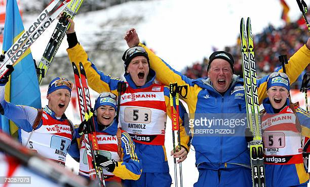 Carl Johan Bergman of Sweden celebrates with teammates Anna Carin Olofsson Bjorn Ferry coach Staffan Eklund and Helena Jonsson in finish area of the...