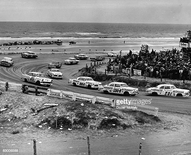 Carl Keikhafer cars lead by Buck Bakerin his 1955 Chrysler race through the south turn during the Beach and Road Course race in Daytona Beach Florida...
