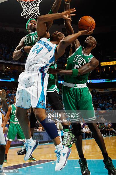 Carl Landry of the New Orleans Hornets shoots the ball over Kevin Garnett of the Boston Celtics at New Orleans Arena on December 28 2011 in New...