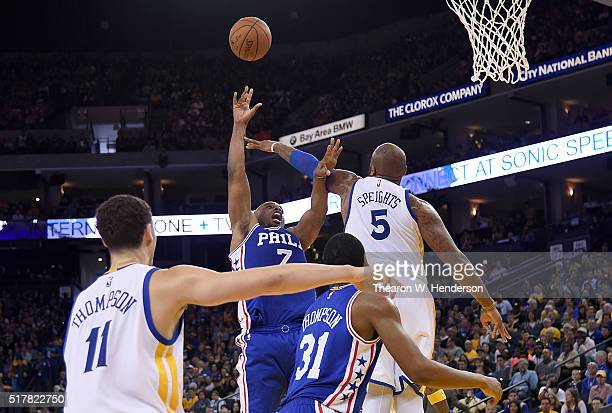 Carl Landry of the Philadelphia 76ers shoots over Marreese Speights of the Golden State Warriors during an NBA Basketball game at ORACLE Arena on...