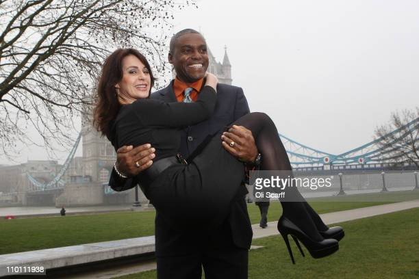 Carl Lewis a former track and field athlete lifts former gymnast Nadia Comaneci outside City Hall following a photocall to officially launch the sale...
