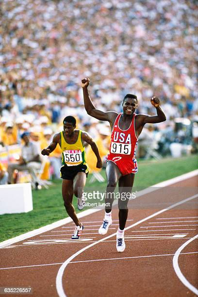 Carl Lewis, at the finish line, thrills a crowd of 92,000 spectators as he wins the gold medal in the men's 100-meter sprint, putting himself on...