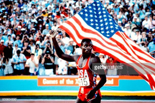 US Carl Lewis holds the American flag after winning the 100m Men's final in 999 at the Los Angeles Olympic games on August 04 1984 Four years later...