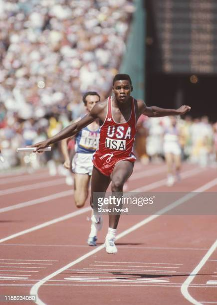 Carl Lewis of the United States carries the baton across the line to win the anchor leg of the Men's 4 x 100 Metres Relay at the XXIII Olympic Summer...