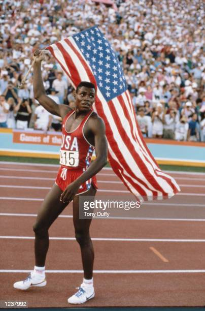 Carl Lewis of the United States carries the stars and stripes flag of the United States of America and celebrates winning the Men's 100 metres sprint...