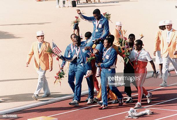 Carl Lewis of the United States is carried on the shoulders of his teammates Calvin Smith Sam Graddy and Ron Brown following the Gold Medal win in...