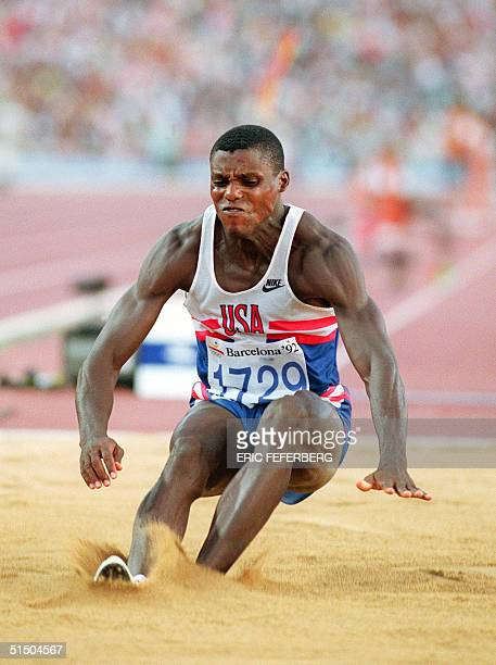 Carl Lewis of the USA lands in the sand during the final of the men's Olympic long jump competition 06 August 1992 in Barcelona Lewis won the gold...