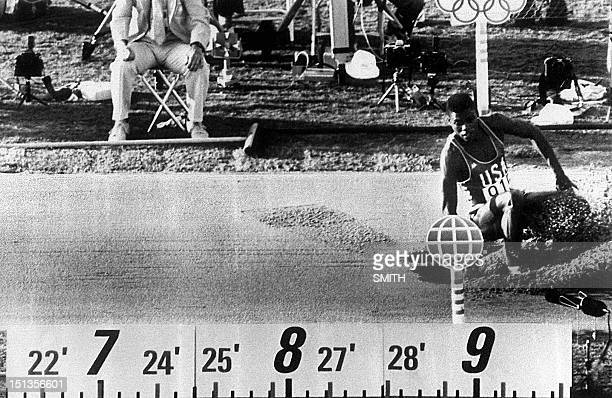 Carl Lewis of the USA lands in the sand pit during the final of the men's Olympic long jump competition 06 August 1984 in Los Angeles Lewis won the...