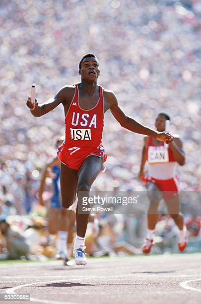 Carl Lewis of the USA raises his arms aloft as he crosses the line to anchor the USA team to victory in the 4 x 100m relay during the 1984 Olympic...