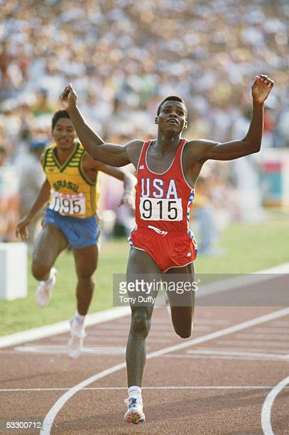 Carl Lewis of the USA raises his arms aloft as he crosses the line to win the 200 metres final during the 1984 Olympic Games at the Colliseum Stadium...