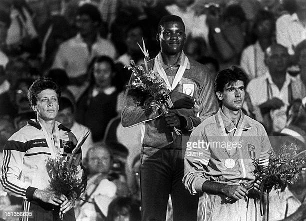 Carl Lewis of the USA smiles on the podium 06 August 1984 in Los Angeles after winning the gold medal in the men's Olympic long jump competition with...