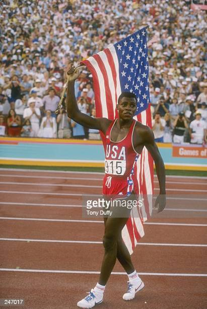 Carl Lewis proudly carries the American flag after completing the 100 meter dash at the Olympic Games in Los Angeles California Lewis won the gold...