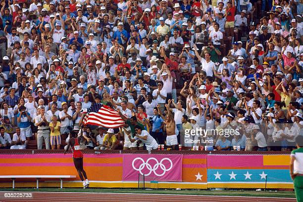 Carl Lewis running with a large American flag displays his patriotism and excites the crowd at the 1984 Summer Olympic Games after winning the men's...