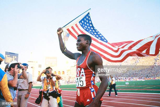 Carl Lewis runs around the stadium with American flag following his first gold medal for 99 second 100 meter dash
