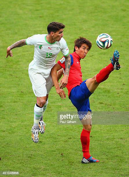Carl Medjani of Algeria competes for the ball with Koo JaCheol of South Korea during the 2014 FIFA World Cup Brazil Group H match between South Korea...