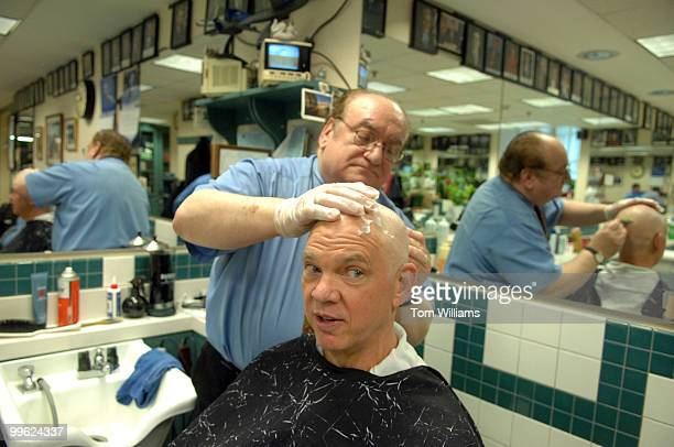 Carl Parks an executive with National Association of Mutual Insurance Companies gets his head shaved by Mario D'Angelo in the Senate barber shop in...