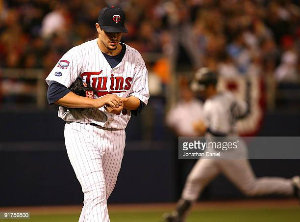 Carl Pavano of the Minnesota Twins reacts as Jorge Posada of the New York Yankees runs the bases after hitting a solo home run in the 7th inning in...