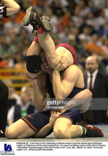 Carl Perry of the University of Illinois works to get the locked legs of Michael Lighter of Oklahoma off his head during their 141pound wrestling...