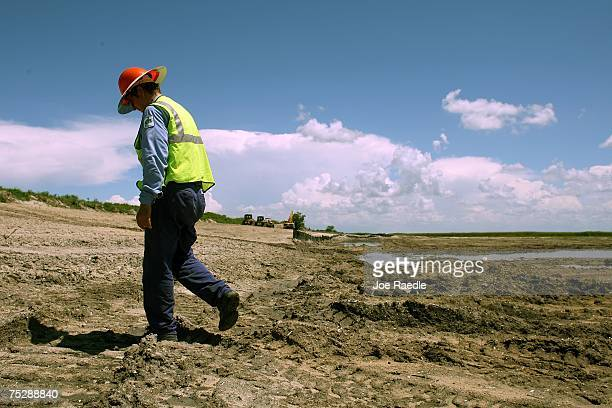 Carl Poorbaugh of the South Florida Water Management District walks through an area of the Lake Okeechobee's driedout shoreline scraped free of muck...