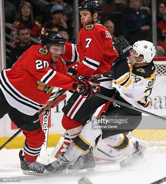 Carl Soderberg of the Boston Bruins collides with Brandon Saad and Brent Seabrook of the Chicago Blackhawks at the United Center on January 19 2014...