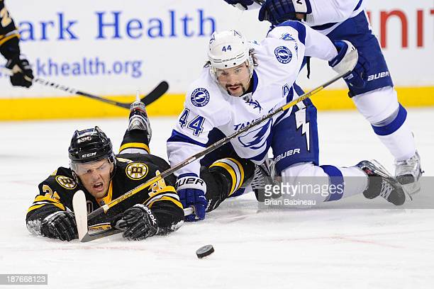 Carl Soderberg of the Boston Bruins fights for the puck against Nate Thompson of the Tampa Bay Lightning at the TD Garden on November 11 2013 in...