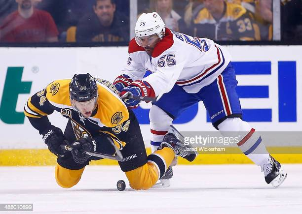 Carl Soderberg of the Boston Bruins is checked from behind with the puck by Francis Bouillon of the Montreal Canadiens in the second period in Game...