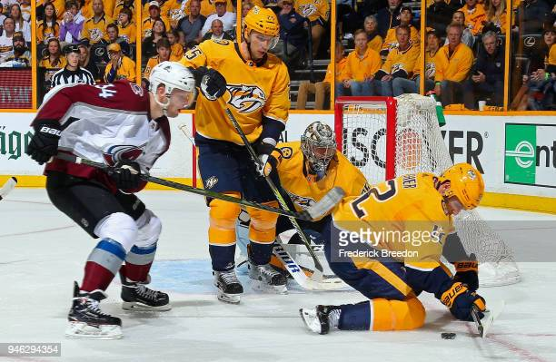 Carl Soderberg of the Colorado Avalanche and Pekka Rinne andAlexei Emelin of the Nashville Predators watch as Mike Fisher tries to control the puck...