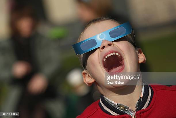 Carl uses special glasses to look into the sky at a partial solar eclipse near the Brandenburg Gate on March 20 2015 in Berlin Germany Over Central...