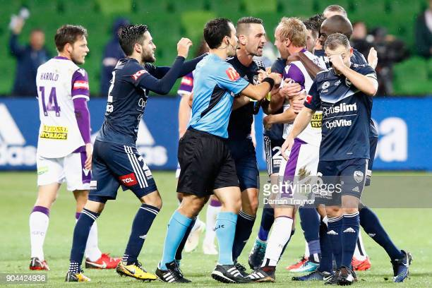 Carl Valeri of Melbourne Victory argues with Mitchell Nichols and Alex Grant of Perth Glory after Grant put a crud tacle on Leroy George of the...