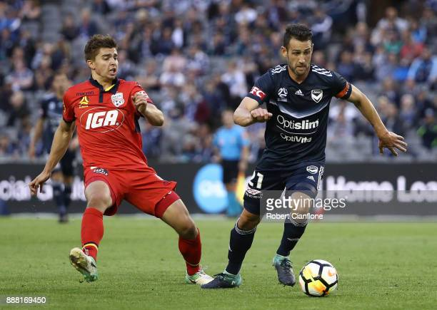Carl Valeri of the Victory is pressured by Nathan Konstandopoulos of Adelaide United during the round 10 ALeague match between the Melbourne Victory...