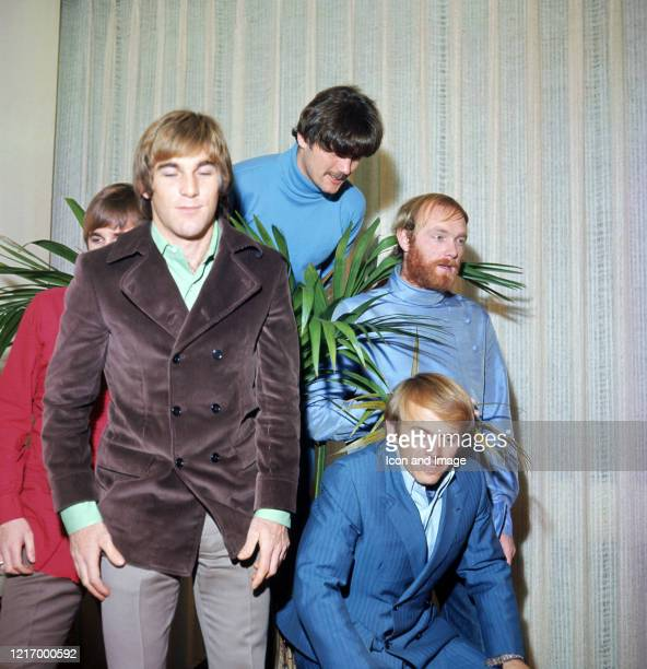 Carl Wilson stands behind Dennis Wilson , Bruce Johnston, Mike Love, and Al Jardine, of American pop group The Beach Boys, in London, England, 1966.