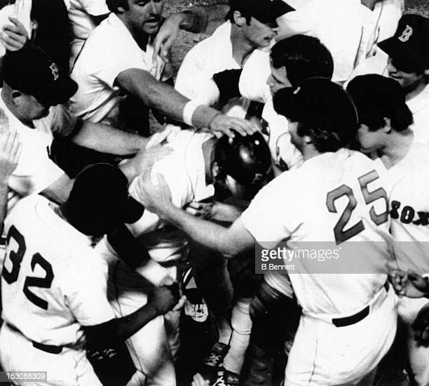 Carl Yastrzemski of the Boston Red Sox is mobbed by his teammates after hitting his 400th career home run against the Oakland Athletics in the 7th...