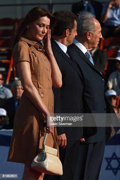 Carla Bruni wife of French President Nicolas Sarkozy stands alongside her husband and Israeli President Shimon Peres during a welcoming ceremony for...