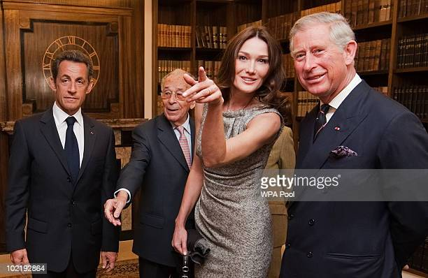Carla Bruni-Sarkozy and her husband, French President Nicolas Sarkozy and Prince Charles, Prince of Wales look at photographs of French President...