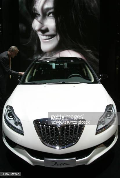 Carla Bruni-Sarkozy, wife of French President Nicholas Sarkozy, appears on a tv screen behind the Lancia Delta on the second press day at the 78th...