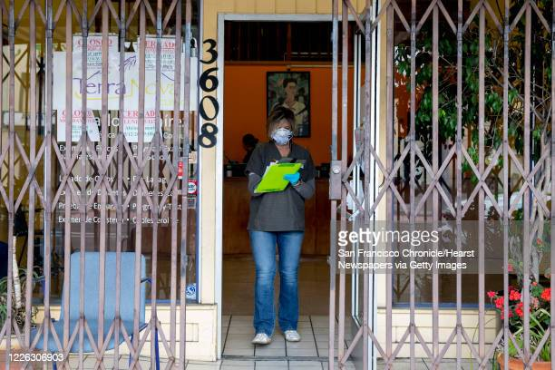 Carla Furtado works to screen and check in patients as they wait in line to be seen at Terra Nova Clinic in the Fruitvale neighborhood of Oakland,...