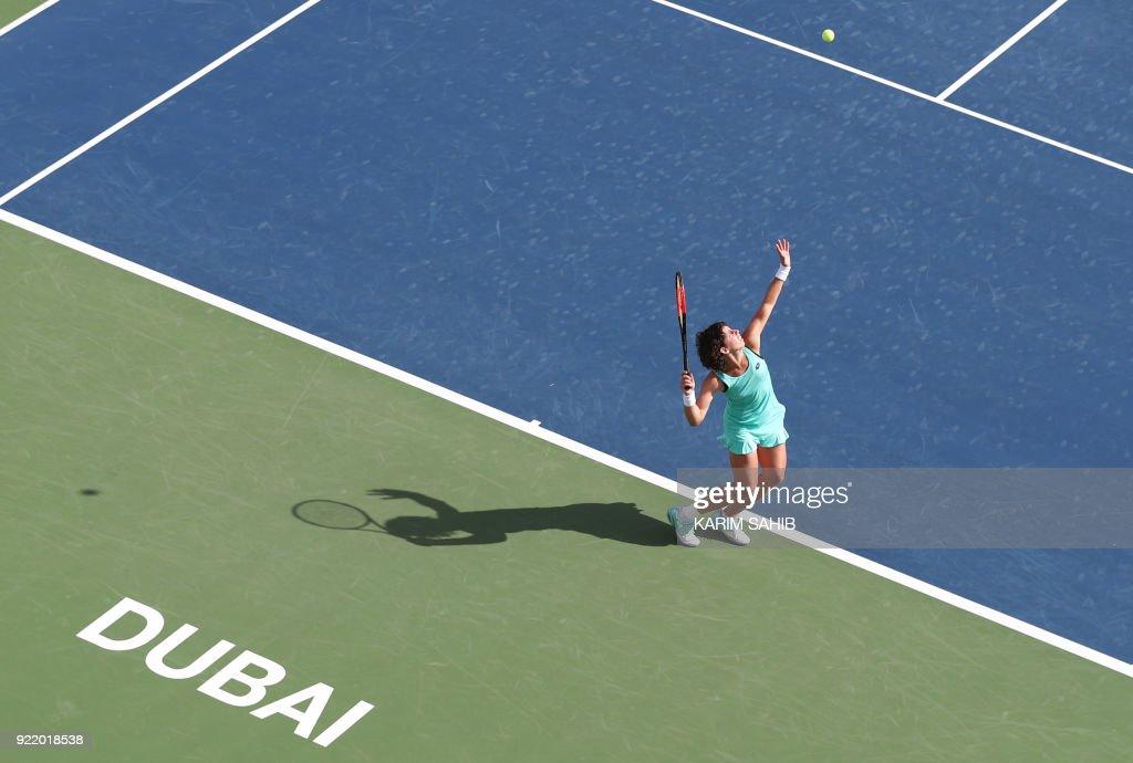 TOPSHOT - Carla Suarez Navarro of Spain returns the ball to Karolina Pliskova of the Czech Republic during day two of the WTA Dubai Duty Free Tennis Championship at the Dubai Tennis Stadium on February 21, 2018. /