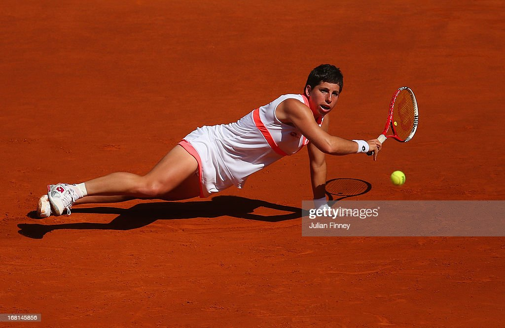 Carla Suarez Navarro of Spain stetches for a shot as she falls to the clay in her match against Sam Stosur of Australia during day three of the Mutua Madrid Open tennis tournament at the Caja Magica on May 6, 2013 in Madrid, Spain.