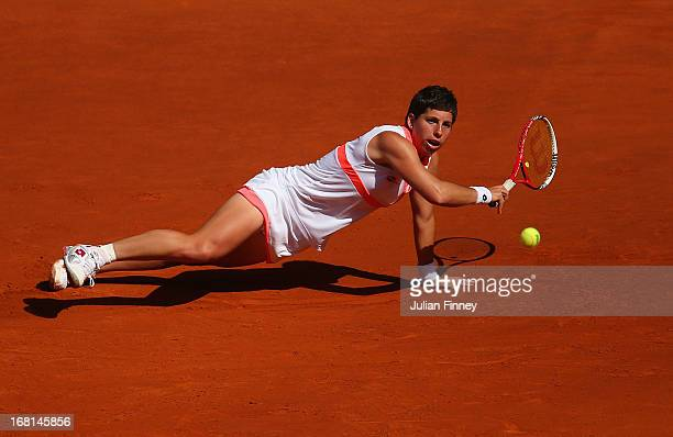 Carla Suarez Navarro of Spain stetches for a shot as she falls to the clay in her match against Sam Stosur of Australia during day three of the Mutua...