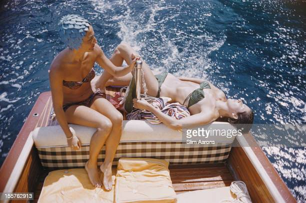 Carla Vuccino wearing a swimming cap and a sunbathing Marina Rava both wearing bikinis as they sit on the rear of a boat on the waters off the coast...