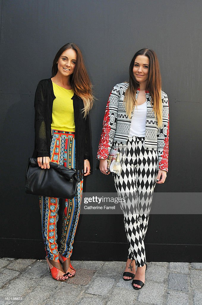 Carla Webster, a fashion merchandiser wearing a Topshop mesh fringed cardigan, River Island geometric print trousers, Zara sandals, Roll down clutch by Zara, and student Hannah CrossKey wears a two tone ASOS suit, the jacket embellished with red applique floral motifs on the sleeves, worn with harlequin diamond patterned trousers, see through clutch by Klear Klutch at London Fashion Week Fall/Winter 2013/14 on February 18, 2013 in London, England.