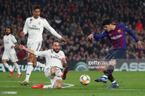 Carles Alena of FC Barcelona shoots towards goal under a challenge by Dani Carvajal of Real Madrid CF during the Copa del Semi Final first leg match...