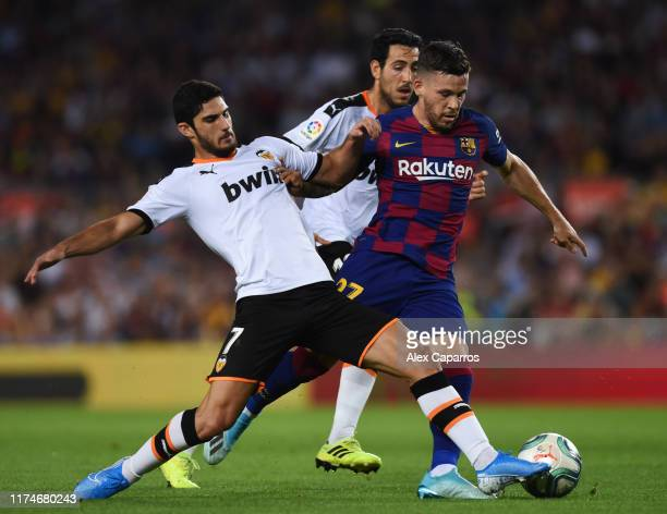 Carles Perez of Barcelona goes between Goncalo Guedes and Daniel Parejo of Valencia during the Liga match between FC Barcelona and Valencia CF at...