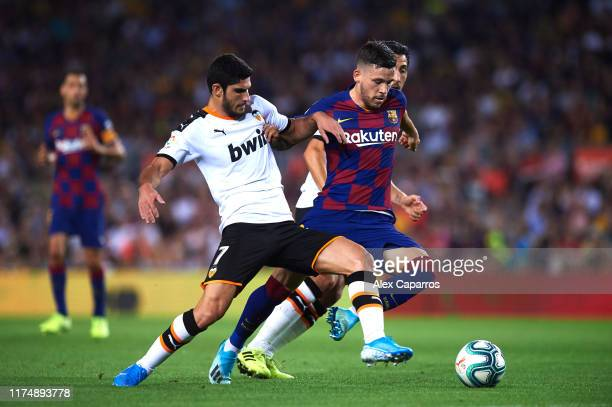 Carles Perez of Barcelona goes between Goncalo Guedes and Daniel Parejo of Valencia CF during the La Liga match between FC Barcelona and Valencia CF...