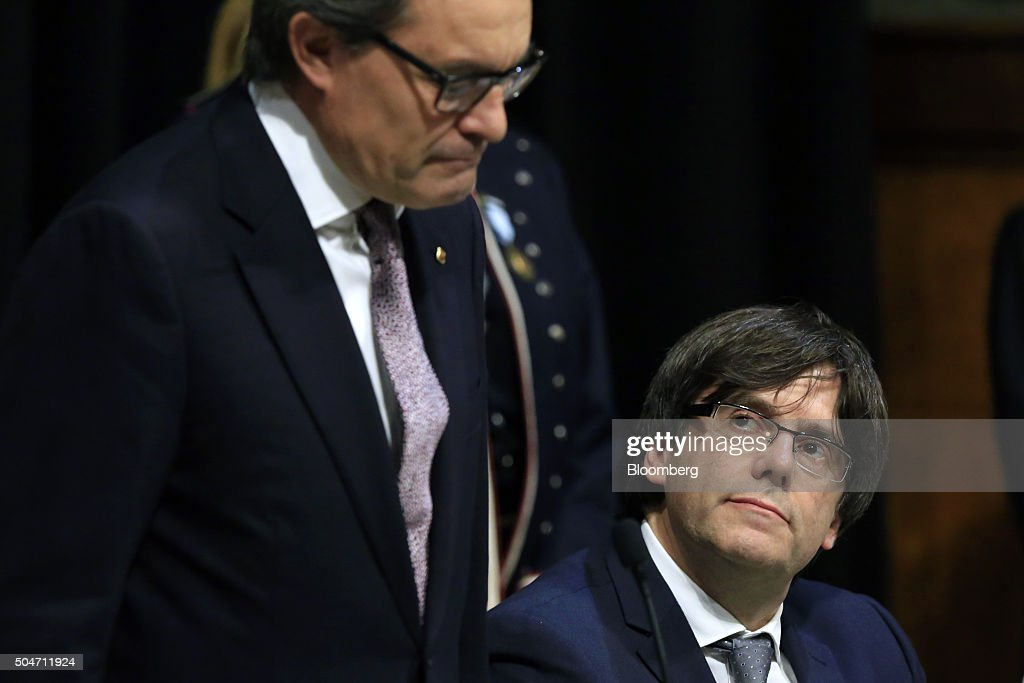 Carles Puigdemont, Catalonia's incoming president, right, listens as Artur Mas, former Catalan acting president, speaks during the swearing in ceremony at the Palau de la Generalitat in Barcelona, Spain, on Tuesday, Jan. 12, 2016. The former mayor of Girona, a city near Spain's border with France, emerged as a last-minute compromise candidate as the fighting between two factions within the independence movement threatened to force new elections, jeopardizing their majority in the regional assembly. Photographer: Pau Barrena/Bloomberg via Getty Images