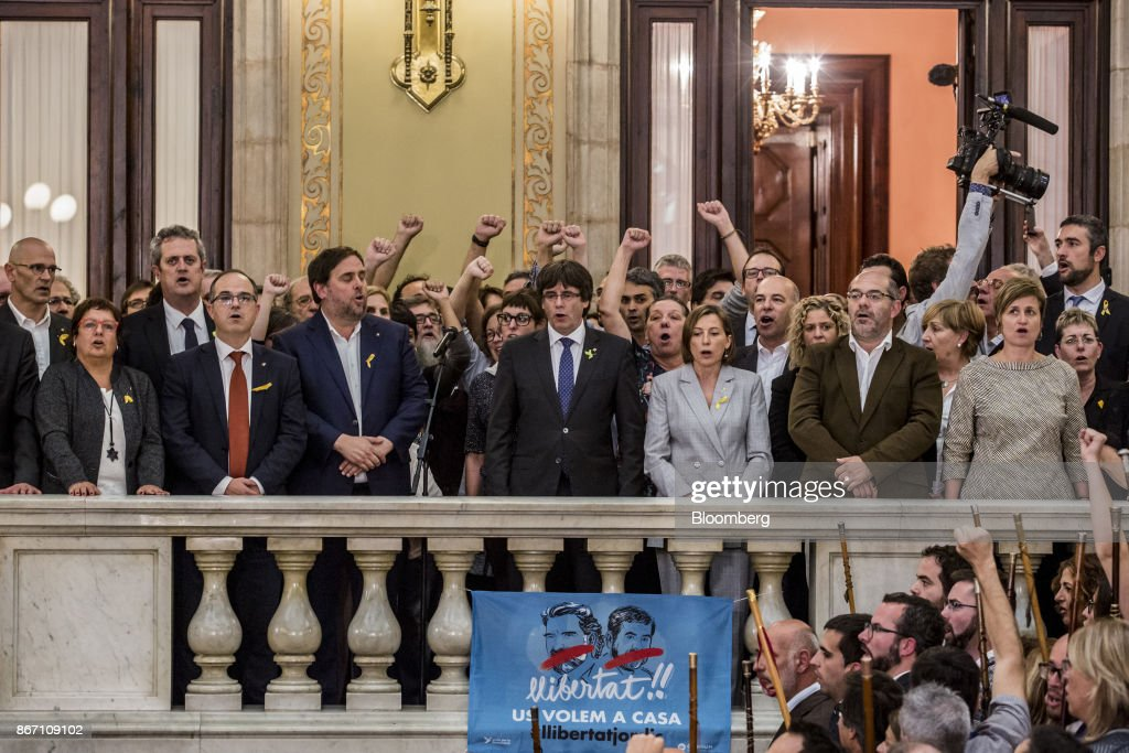 Carles Puigdemont, Catalonia's president, center, and Oriol Junqueras, Catalonia's vice president, center left, sing the Catalan anthem with pro independence Catalan mayors following a vote in favour of independence at the Catalan parliament in Barcelona, Spain, on Friday, Oct. 27, 2017. The resolution approved by lawmakers in Barcelona said the establishment of Europes newest sovereign country had been set in motion. Photographer: Angel Garcia/Bloomberg via Getty Images