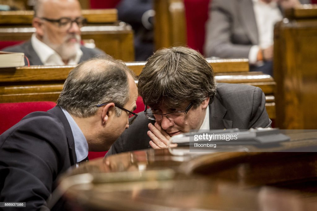 Carles Puigdemont, Catalonia's president, right, speaks to a colleague during a debate at the Catalan parliament in Barcelona, Spain, on Thursday, Oct. 26, 2017. Catalonia's president says he won't call a regional election that could have defused tension with Spain. Photographer: Angel Garcia/Bloomberg via Getty Images