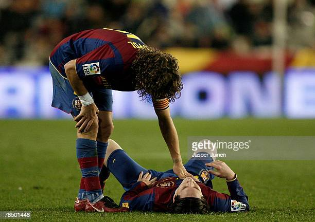 Carles Puyol of Barcelona comforts his injured teammate Lionel Messi laying on the pitch before abandoning the match during the La Liga match between...